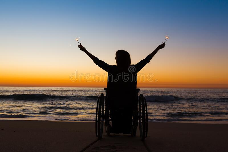 Handicapped woman holding fire sparklers stock images