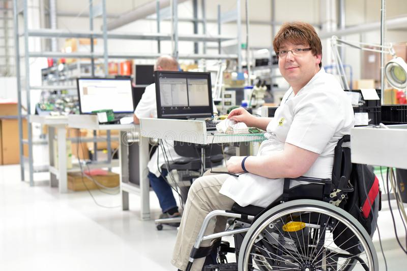 handicapped worker in a wheelchair assembling electronic components in a modern factory at the workplace royalty free stock image