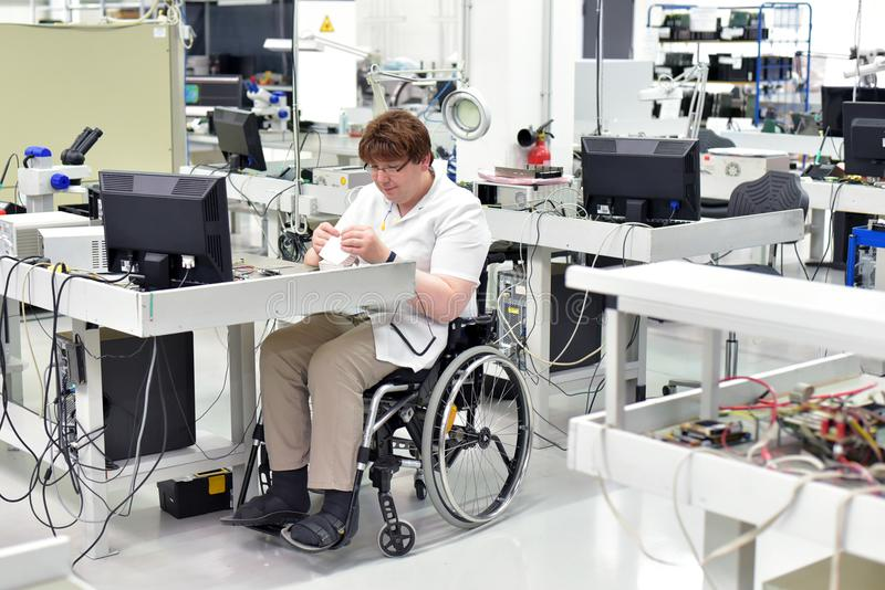 handicapped worker in a wheelchair assembling electronic components in a modern factory at the workplace royalty free stock photography