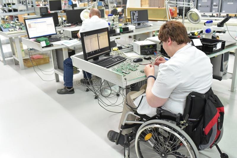 Handicapped worker in a wheelchair assembling electronic compone stock images
