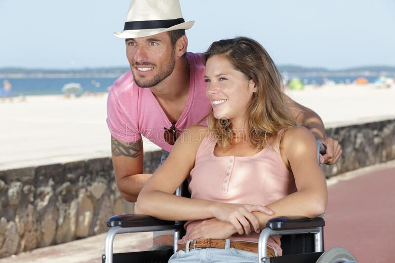 Handicapped young couple resting on beach stock image
