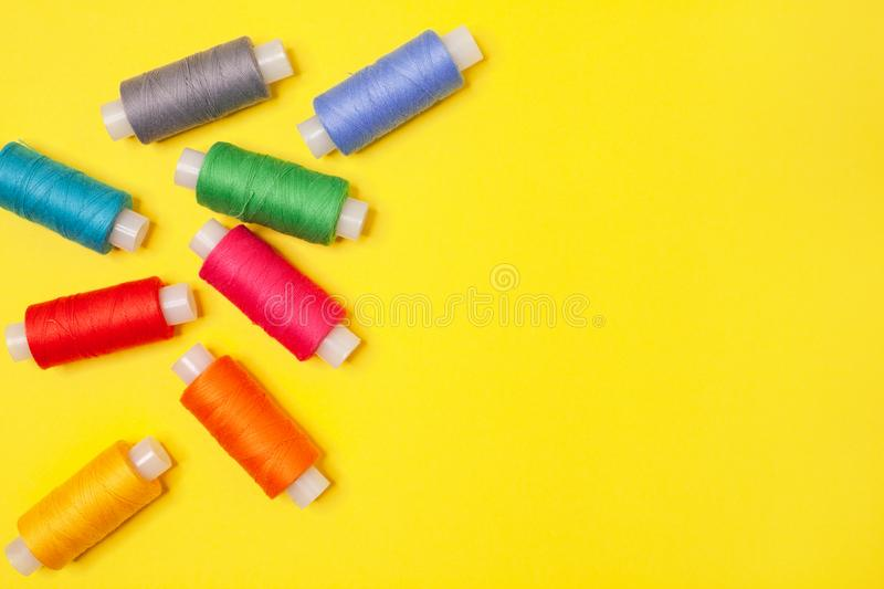 Handicraft background. Set of multicolored spools of thread on yellow background with copy space. Accessories for needlework stock photos