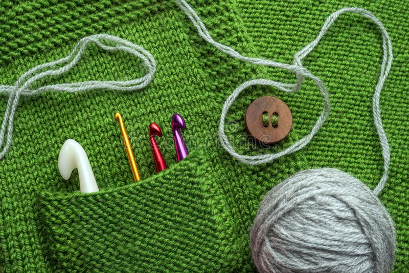 Handicraft background. Steel and plastic crochet hooks in the pocket of knitting sweater. Handmade background. Craft stock photography
