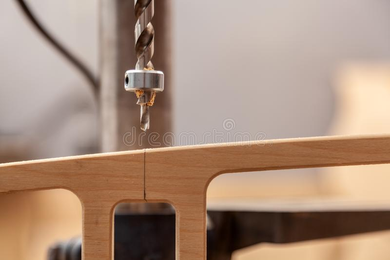 Handicraft Carpentry. Close up of a man with work clothes and a carpenter`s hat is carving a wooden board on an  large drilling machine in a light workshop stock photography