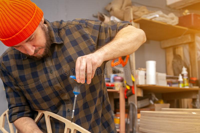 Handicraft Carpentry. Home repair concepts, close up. Handicraft Carpentry. Cabinet-maker hands drilling a wooden plank using turn-screw on the working table in stock image