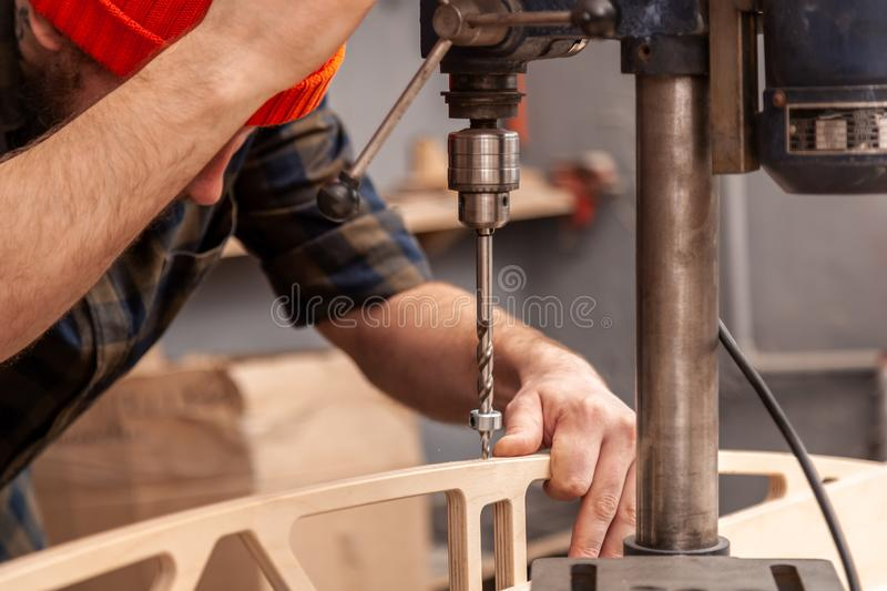 Handicraft Carpentry. Home repair concepts, close up. Handicraft Carpentry. Cabinet-maker hands drilling a wooden plank using electric drill on the working table stock photos