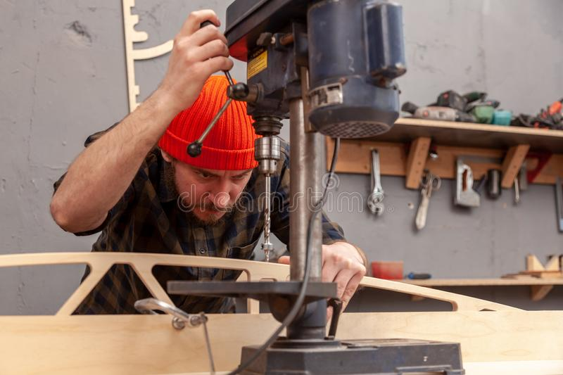 Handicraft Carpentry. Home repair concepts, close up. Handicraft Carpentry. Cabinet-maker hands drilling a wooden plank using electric drill on the working table stock photography