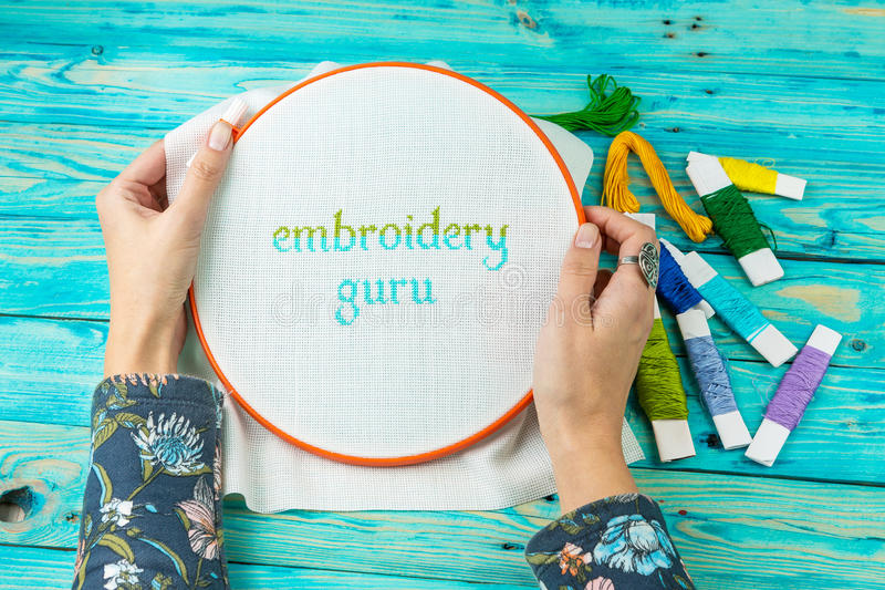 Handicraft handmade lettering Embroidery Guru. Women's hands hold the hoop from the embroidery lettering embroidery Guru. Blue wood background. Obsessed hobbies stock photos