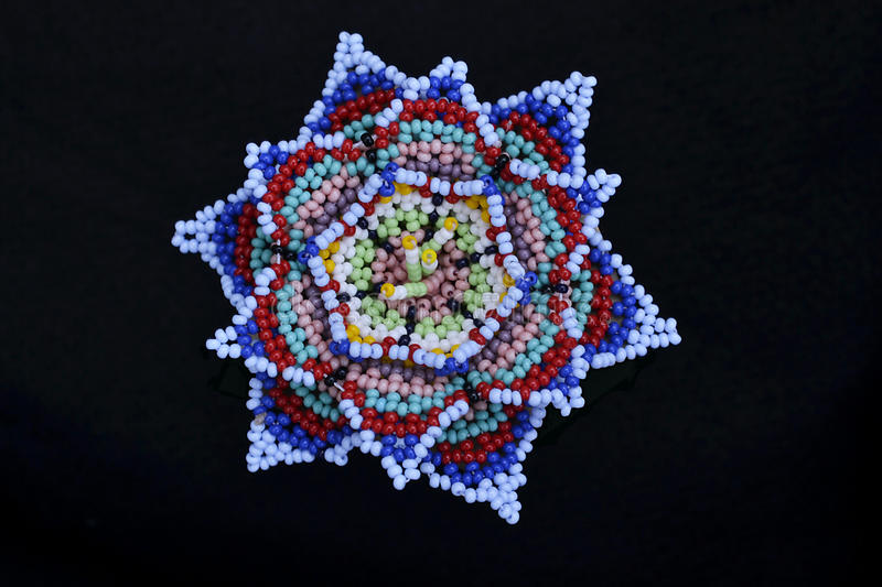 Handicrafts huichol. Colorful mexican craftwork created by huichol people in Jalisco, Mexico.Tiny beads are handwoven to create their sacred flower royalty free stock photos