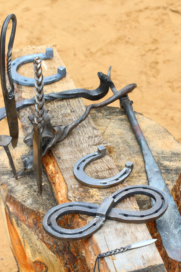 Handicrafts knives, horseshoes on wooden stump royalty free stock images