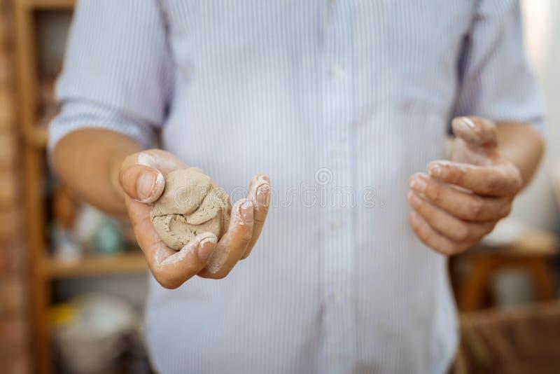 Handicraftsman, das Handvoll Töpferware für seine Handarbeit hat lizenzfreie stockfotos
