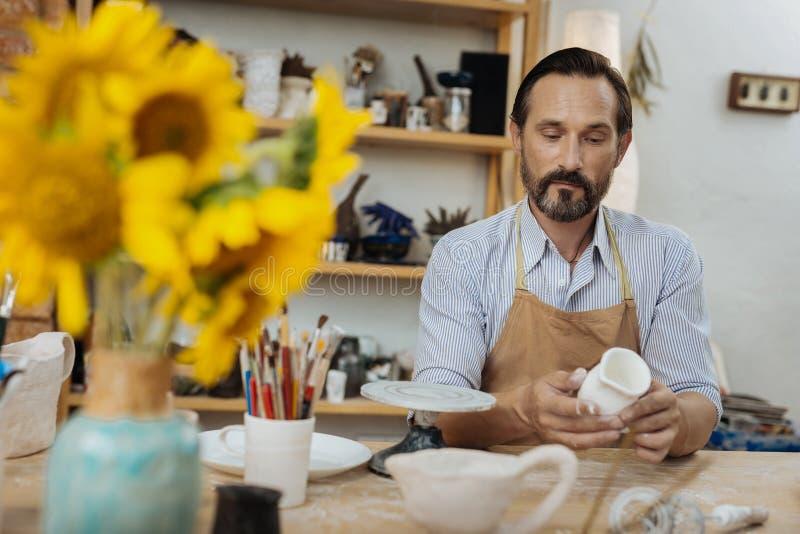 Handicraftsman, das am Tisch mit dem Vase voll von den Sonnenblumen sitzt lizenzfreie stockbilder