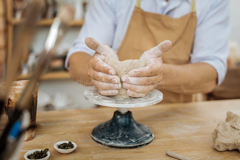 Handicraftsman, das Vase mit seinen Händen auf Töpferscheibe bildet stockfotografie