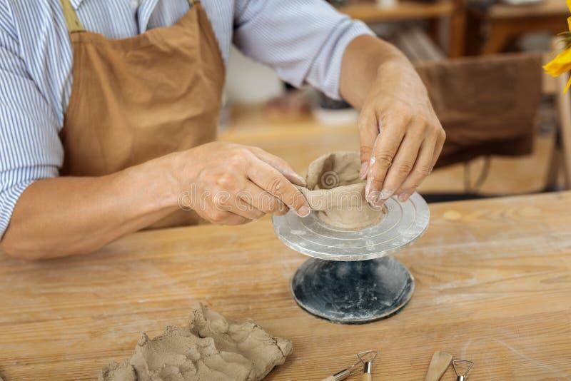 Handicraftsman die schort dragen die met aardewerkwiel werken royalty-vrije stock fotografie