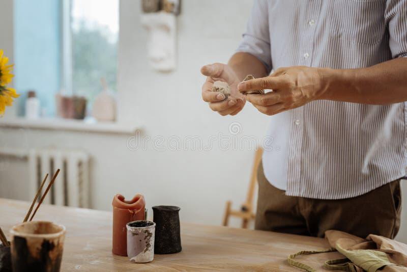 Handicraftsman que hace los pequeños potes para las plantas de la casa foto de archivo
