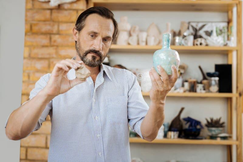 Handicraftsman que mira el florero de cerámica agradable mientras que hace uno más fotos de archivo libres de regalías