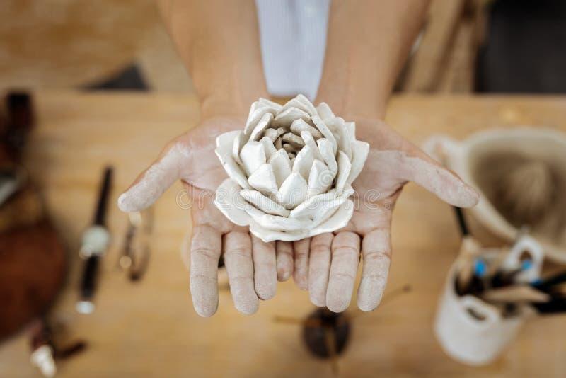 Handicraftsman que mostra uma flor surpreendente do produto de cerâmica nas mãos foto de stock royalty free