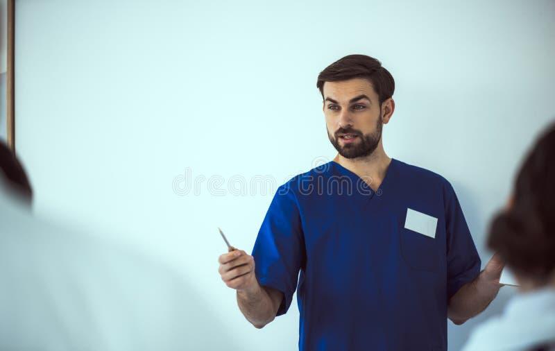 Handige arts die tijdens de conferentie met collega's communiceert royalty-vrije stock afbeelding