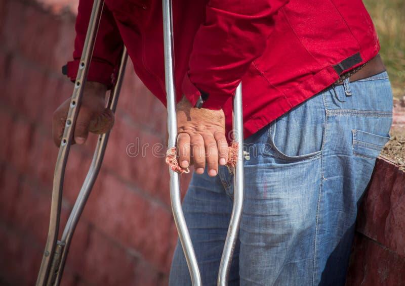 Handikapp med kryckor i händerna av gatan royaltyfri fotografi