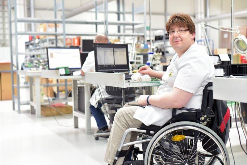 Handikappad arbetare i en rullstol som monterar elektronisk compone royaltyfri bild