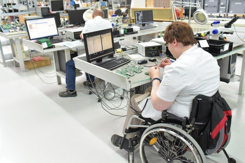 Handikappad arbetare i en rullstol som monterar elektronisk compone arkivbilder