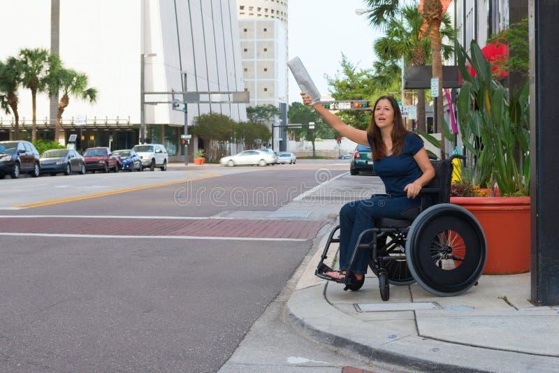 Handikappad kvinna i en rullstol som välkomnar en vinkande newspape för taxi arkivbilder