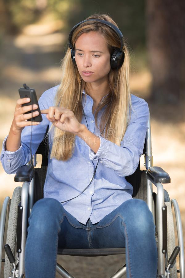 Handikappad kvinna på rullstolen som lyssnar till musik royaltyfri fotografi