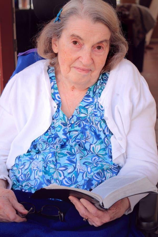 Handikappad kvinna som rymmer en bibel royaltyfria foton