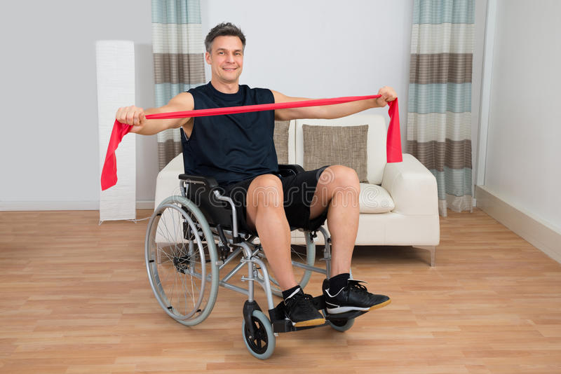 Handikappad man på rullstolen som övar med motståndsmusikbandet royaltyfri foto