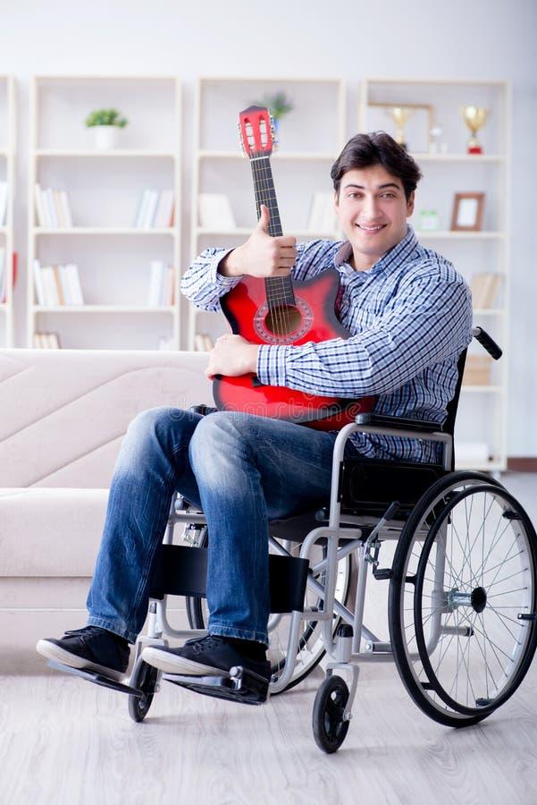 Handikappade personermannen som hemma spelar gitarren royaltyfria bilder