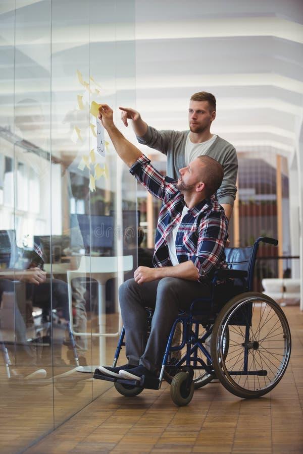 Handikappaffärsman med kollegan som i regeringsställning klibbar bindemedelanmärkningar arkivfoto