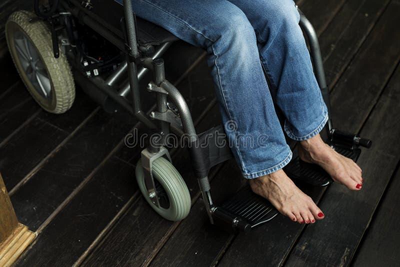 Handikappat kvinnasammanträde på en rullstol arkivbilder