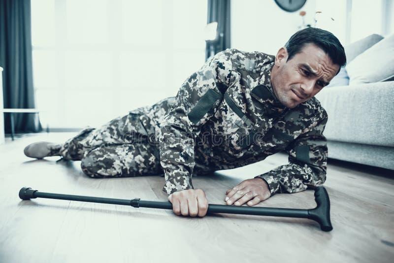 Handikappat militärt ligga på golv med kryckan arkivfoton
