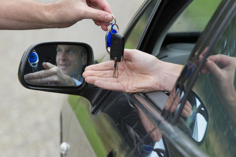 Handing the keys. A hand handing over the car keys to a male driver in a car royalty free stock photo