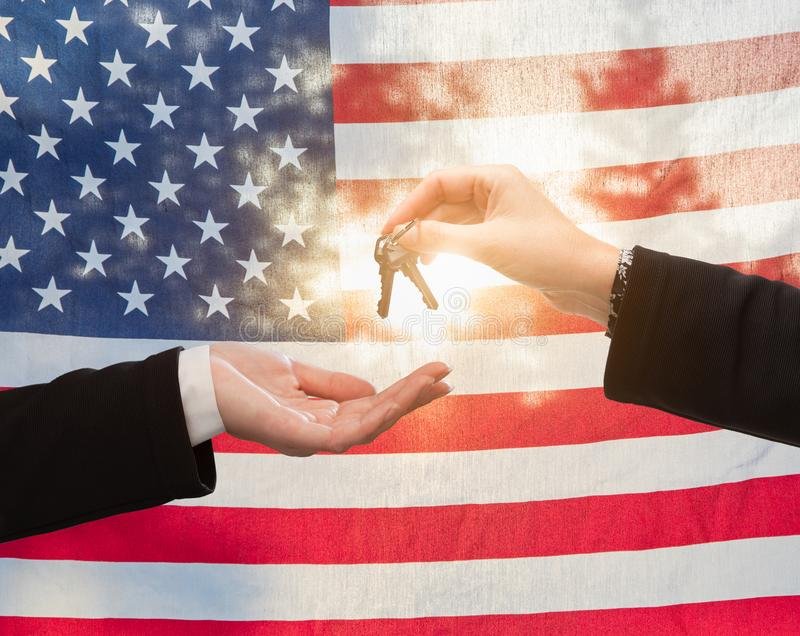 Handing Over House Keys In Front of American Flag. Handing Over House Keys In Front of a Backlit American Flag royalty free stock photos