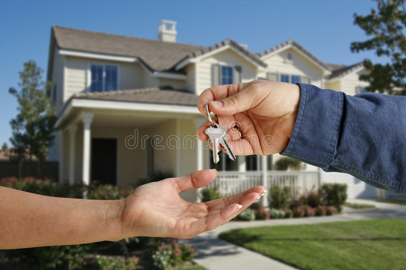 Handing Over the House Keys in Front of New Home stock photo