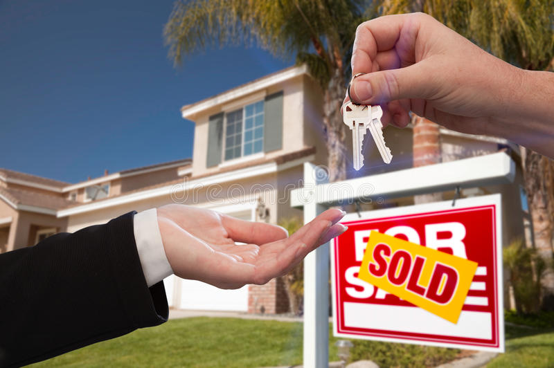 Handing Over the House Keys in Front of New Home royalty free stock photos