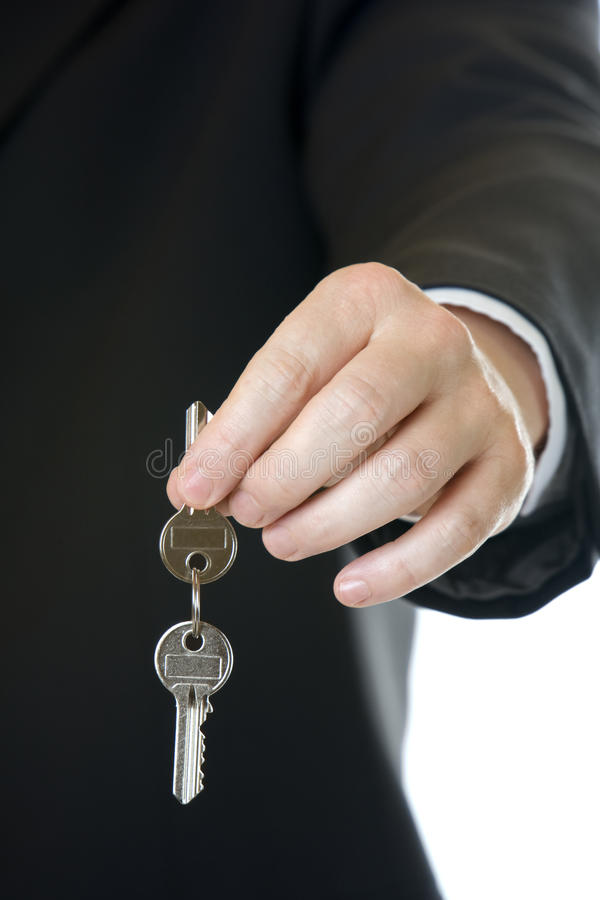 Handing over the key. Businessman holding key in his hand to overgive it stock photos