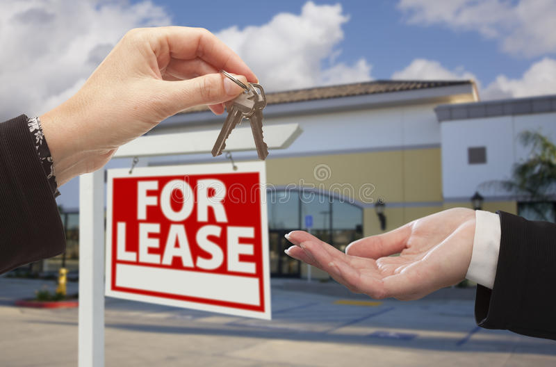 Handing Over Keys in Front of Business Office and Sign. Real Estate Agent Handing Over the Keys in Front of Vacant Business Office and For Lease Sign stock photos