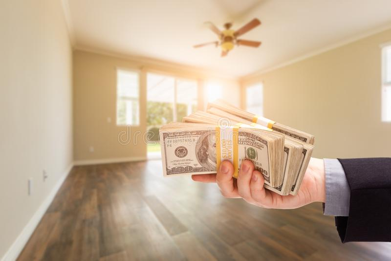 Handing Over Thousands of Dollars In Empty Room of House royalty free stock photo