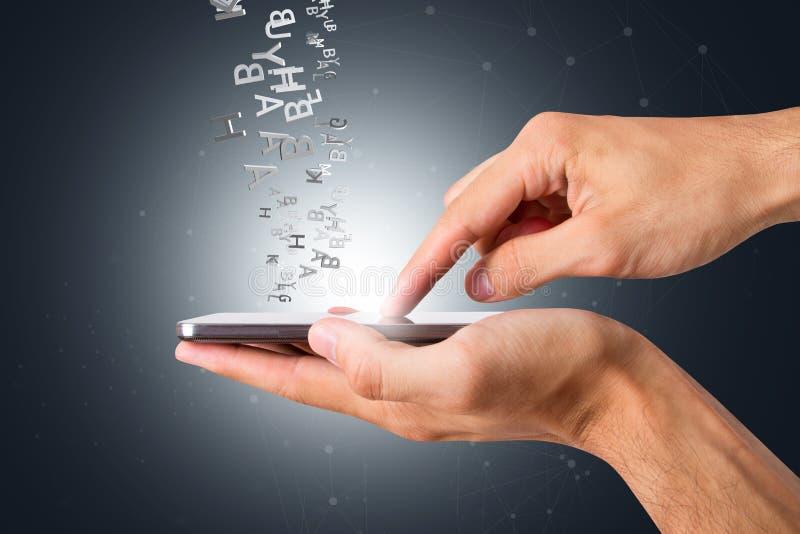 Handinnehav och rörande smart telefon med alfabetbokstaven som omkring flyger arkivbild