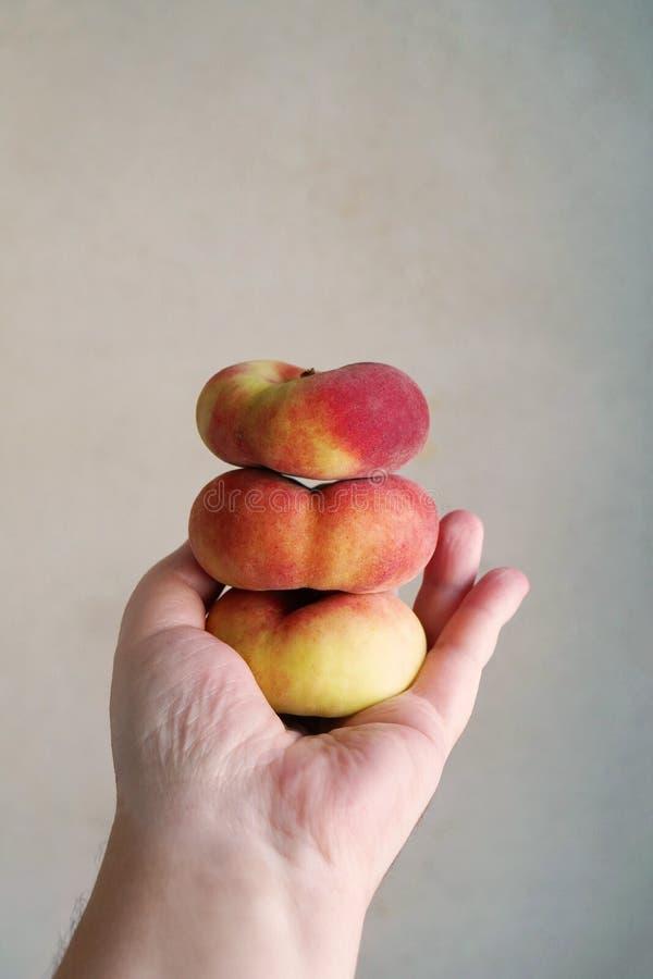 Handinnehavbunt av plana persikor royaltyfri foto