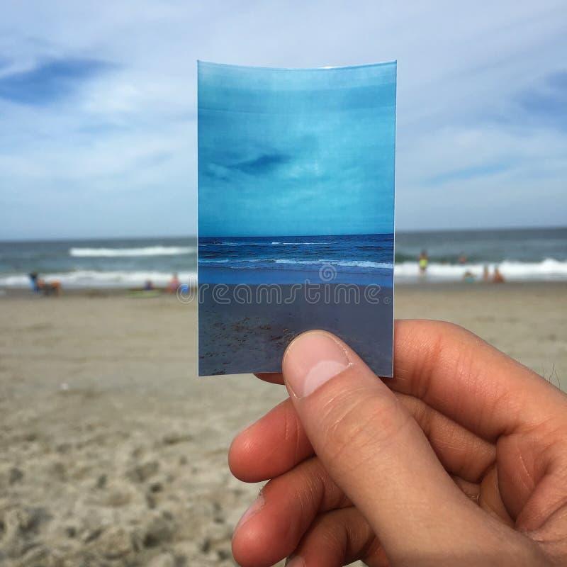 Handinnehavfoto av stranden royaltyfri fotografi