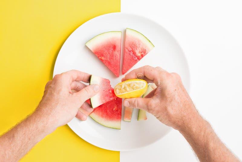 Handinnehavskiva av vattenmelon omkring som pressar citronen över den arkivfoton