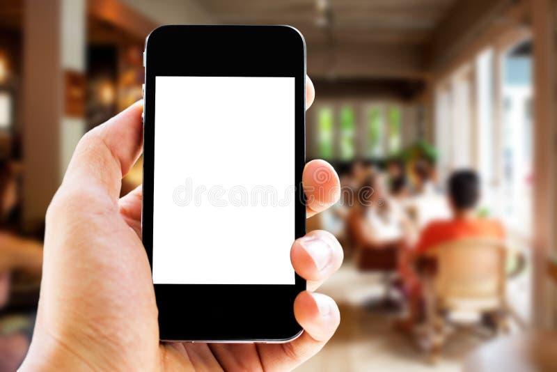 Handinnehavtelefon på kafébakgrund royaltyfri foto