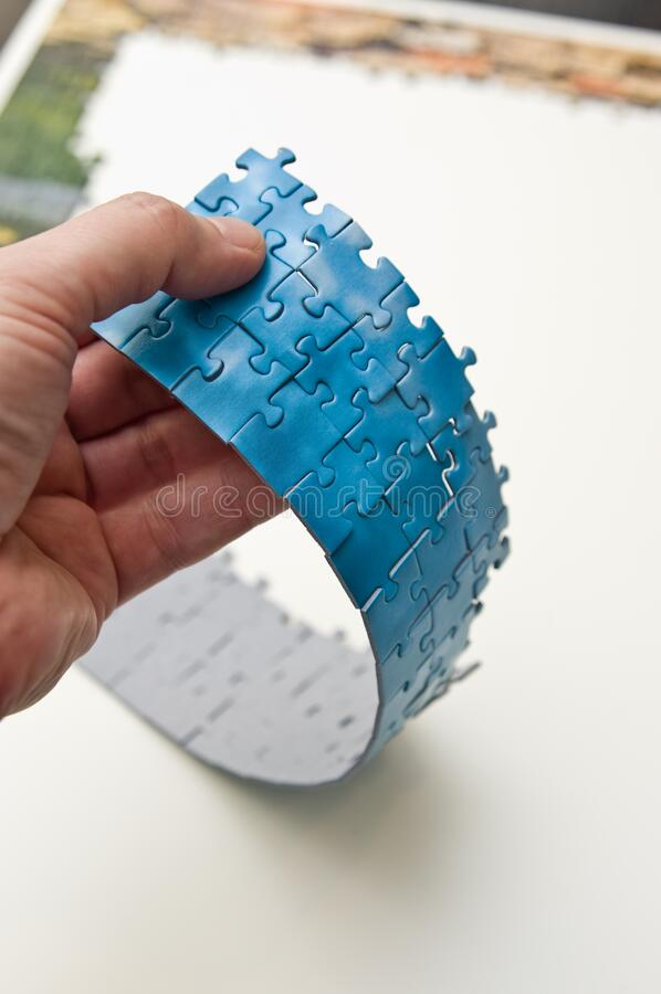 Handje met een streep blauwe puzzelstukjes stock fotografie