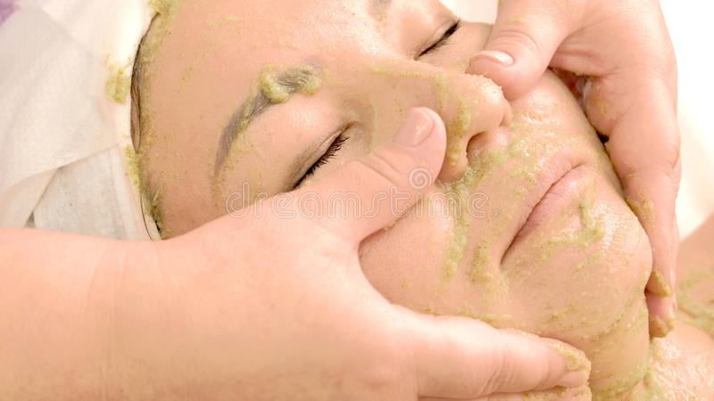 Handkosmetiker, der eine Maske von Kiwisamen im Gesicht des Mädchens reibt Asiatin nimmt Schönheitsbehandlungen Das Konzept von C stockfotos
