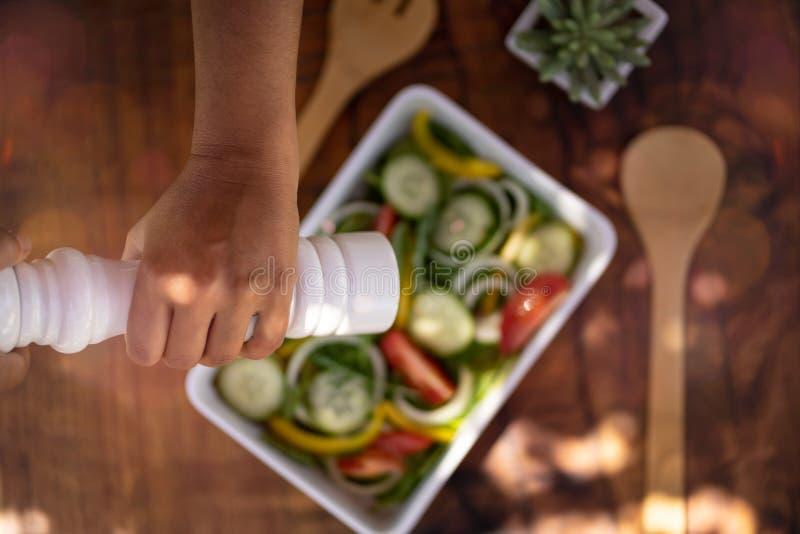 Handkryddning med en vit pepparskakare en färsk sallad med gurka, spenat, rosmarin, lök och tomat Träet oskarp arkivbild