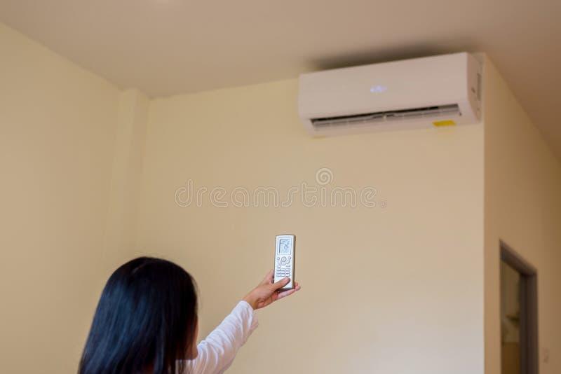 Handkvinna som använder fjärrstyrning för att aktivera 25 grader celsius,Koncept spara energi och spara världen royaltyfria foton