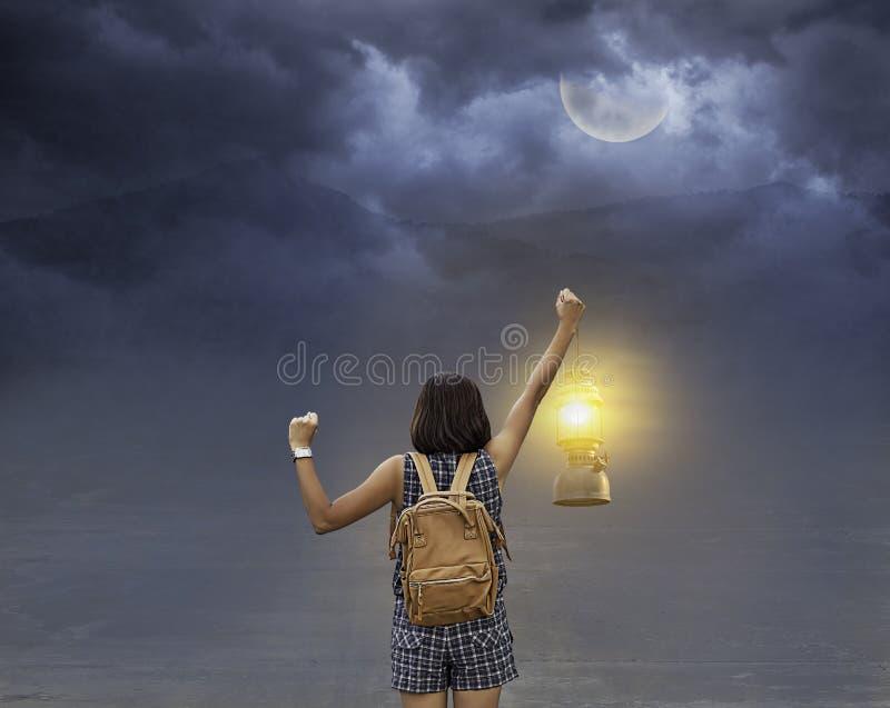 Handkvinna som rymmer den gamla lyktabakgrundsmånen och skuggan av berget på natten med det svarta molnet royaltyfri bild